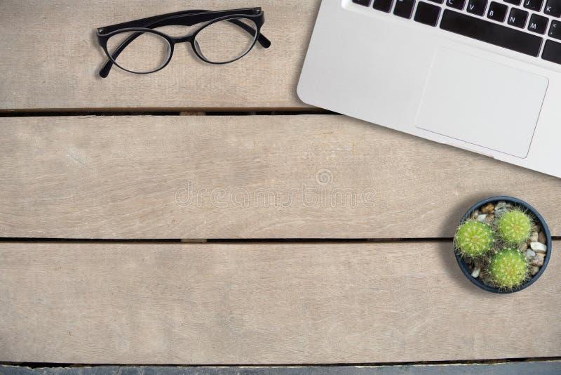 Derida sui vetri e sul computer portatile sulla tavola di legno della vista marrone e superiore fotografie stock