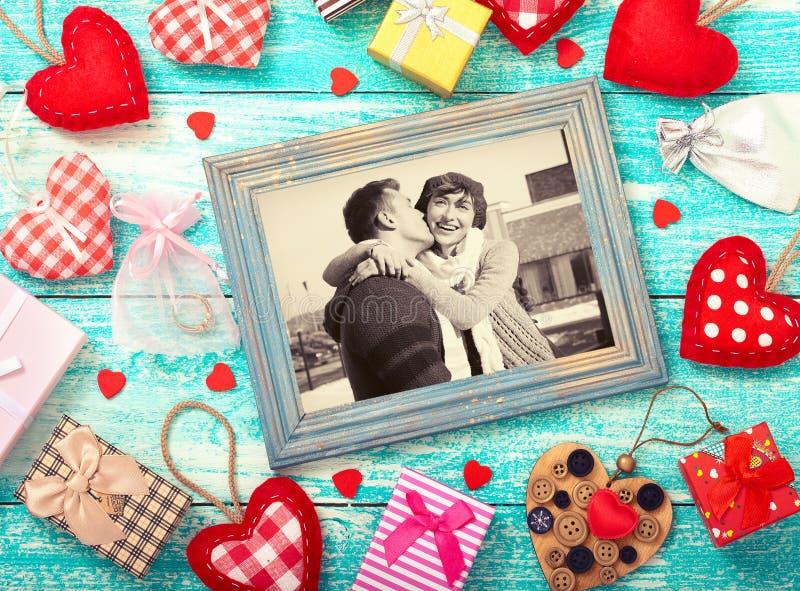Derida sulla struttura del modello per il San Valentino con le forme del cuore Giovani coppie felici nella cornice fotografia stock