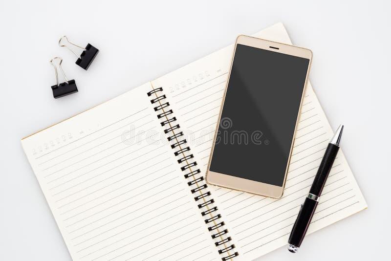 Derida sullo schermo in bianco dello smartphone sul taccuino con la penna su fondo bianco Vista superiore di disposizione piana c fotografia stock