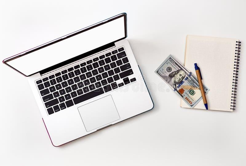 Derida sullo schermo e sui soldi del computer portatile sul taccuino bianco fotografia stock libera da diritti