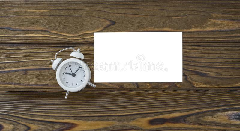 Derisione bianca del biglietto da visita della sveglia e della rete dell'orologio su, foglio di carta pulito su fondo di legno fotografia stock