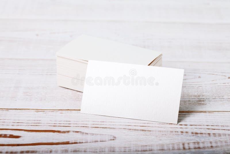 Derisione bianca spessa del biglietto da visita della carta di cotone su sulla piattaforma di legno d'annata fotografia stock