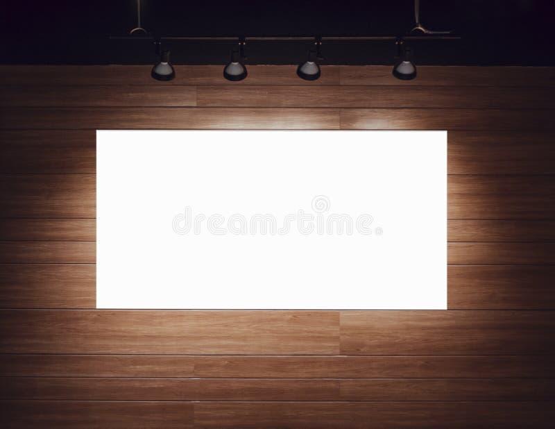 Derisione in bianco del manifesto dell'insegna su sulla parete di legno con la luce del punto immagine stock libera da diritti