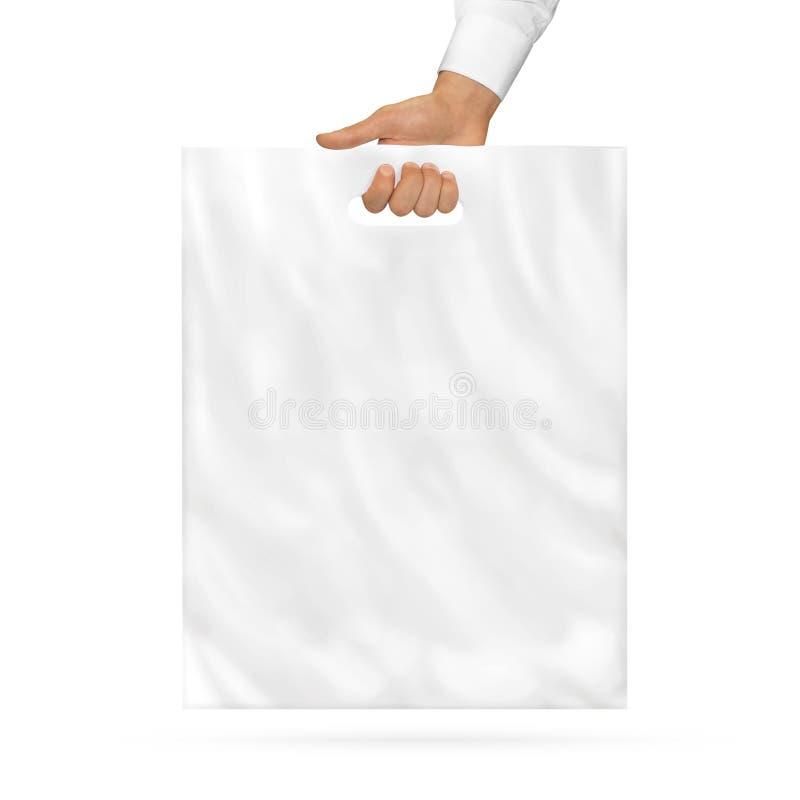 Derisione in bianco del sacchetto di plastica sulla tenuta a disposizione fotografia stock libera da diritti