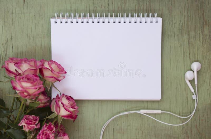 Derisione in bianco del taccuino su per materiale illustrativo con le rose rosa Posto per testo Cuffie di bianco di American Nati fotografia stock