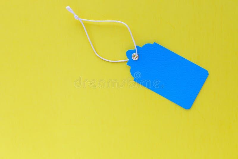 Derisione blu in bianco dell'etichetta di vendita su isolata su fondo giallo luminoso immagine stock libera da diritti