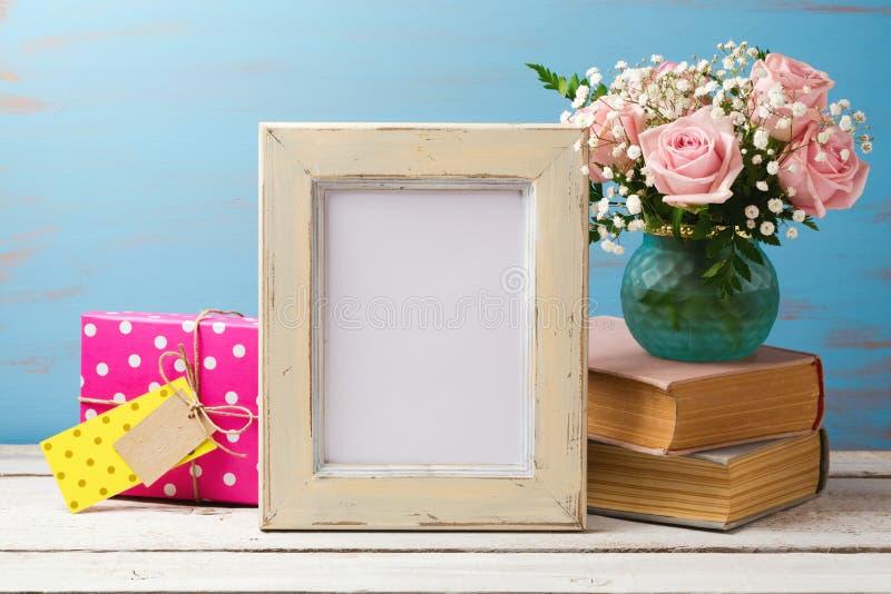 Derisione del manifesto sul modello con il mazzo del fiore, il contenitore di regalo ed i libri rosa immagine stock libera da diritti
