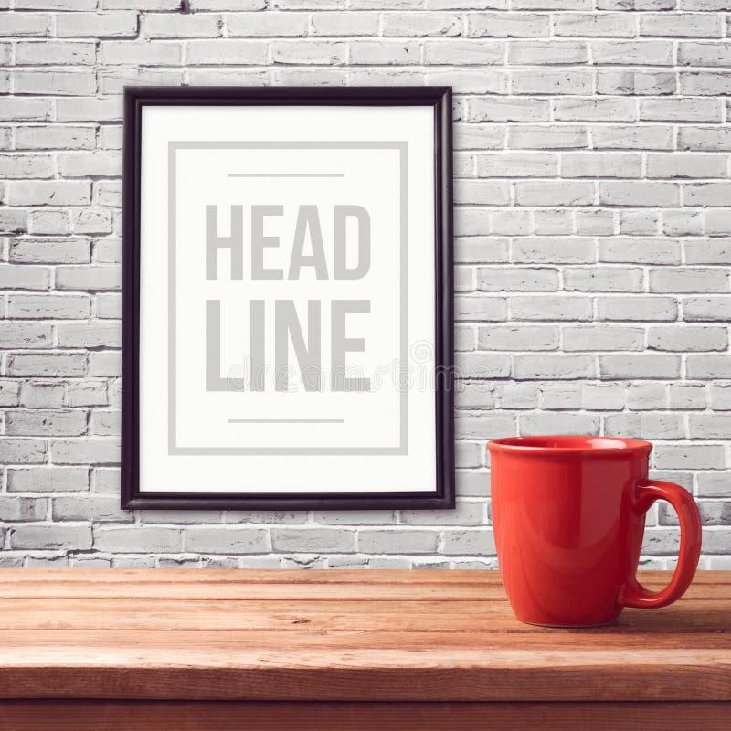 Derisione del manifesto sul modello con la tazza rossa sulla tavola di legno sopra la parete di bianco del mattone immagine stock