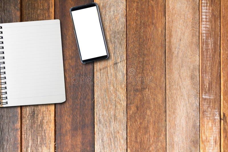 Derisione del telefono cellulare su sullo schermo e sul libro vuoto sulla tavola di legno, angolo di vista superiore immagini stock