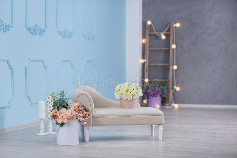 Derisione dell'interno sulla foto Parete blu con il sofà ed il vaso materiali di cuoio del divano con i fiori e la scala della pi immagine stock libera da diritti