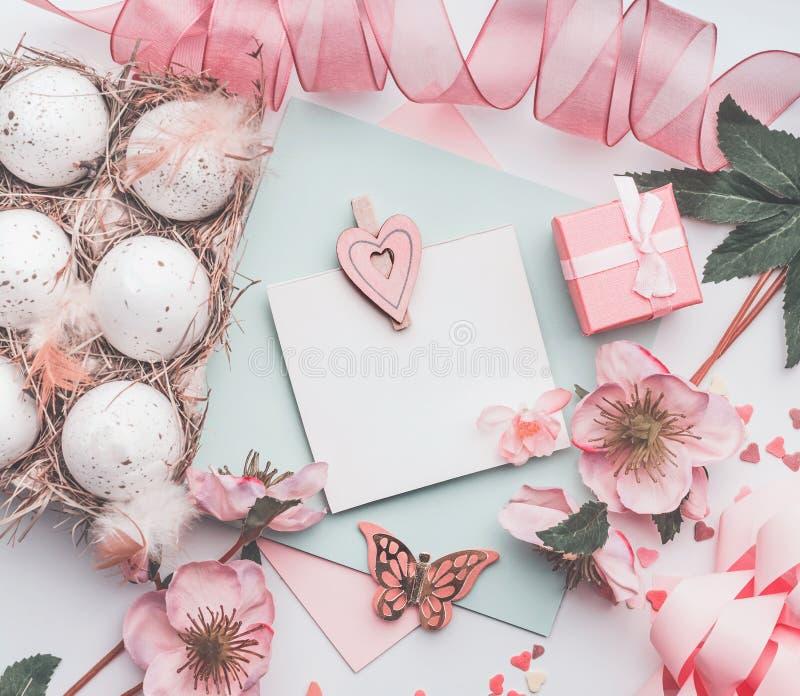 Derisione della cartolina d'auguri di Pasqua su con la scatola delle uova, il nastro rosa, il contenitore di regalo e la decorazi fotografia stock