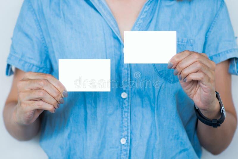 Derisione della tenuta della mano della donna di affari sulla carta di nome fotografia stock libera da diritti