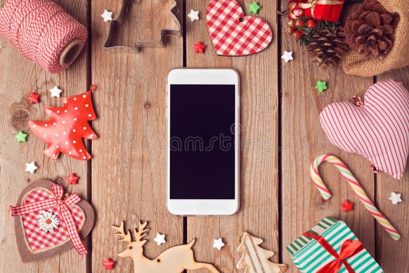 Derisione dello Smart Phone su con le decorazioni rustiche di Natale per la presentazione di app Vista da sopra immagini stock libere da diritti