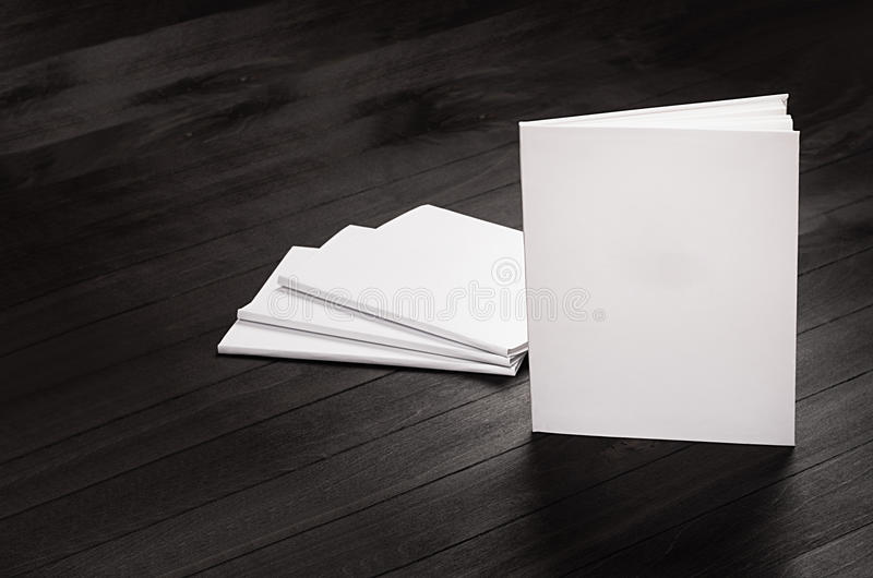 Derisione di identità corporativa su delle riviste in bianco che stanno sul fondo di legno alla moda nero, modello immagine stock libera da diritti