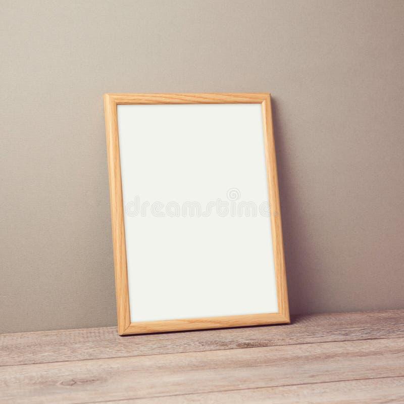 Derisione di legno della struttura del manifesto sul modello sopra la parete fotografia stock libera da diritti