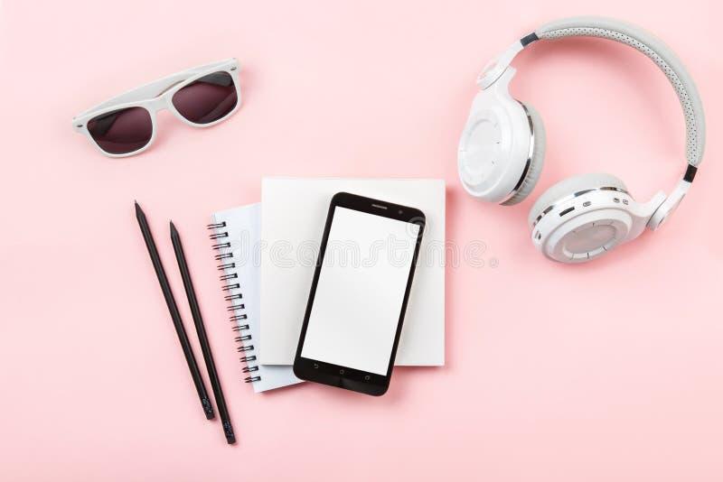 Derisione di vista superiore sul telefono, sulle cuffie e sui vetri su fondo rosa immagine stock libera da diritti