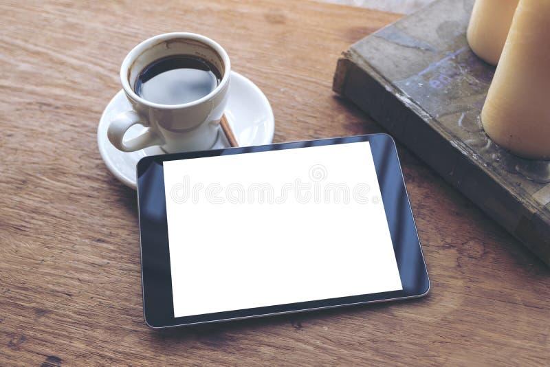 Derisione di vista superiore sull'immagine della compressa nera con la tazza da tavolino in bianco bianca di caffè e dello scherm fotografie stock libere da diritti