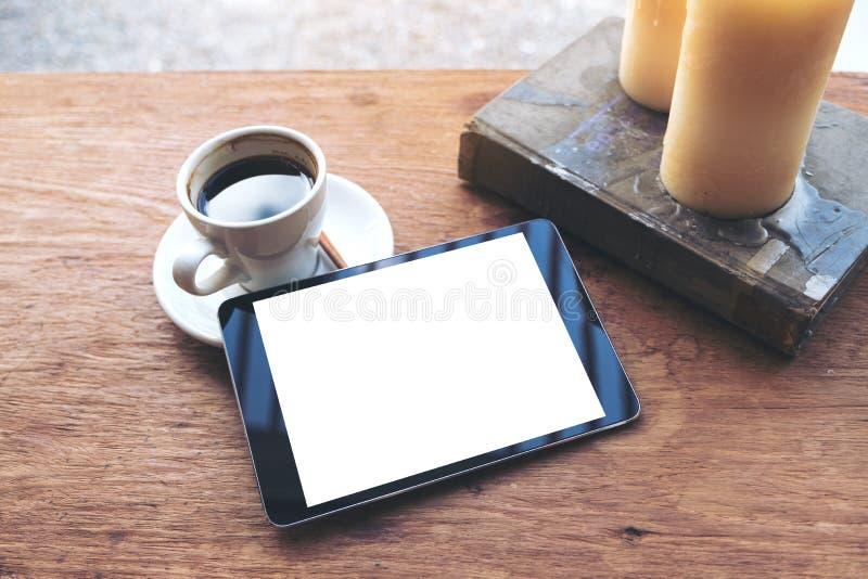 Derisione di vista superiore sull'immagine della compressa nera con la tazza da tavolino in bianco bianca di caffè e dello scherm immagini stock