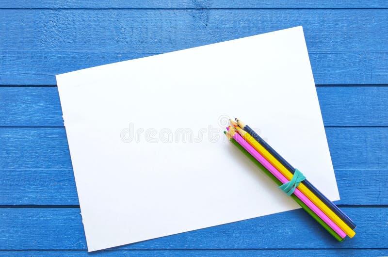 Derisione su materiale illustrativo per il disegno e testo su un fondo di legno blu con quattro matite colorate sull'angolo dello fotografie stock