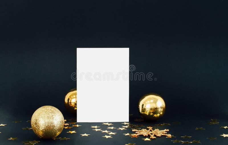 Derisione sulla carta del greeteng su fondo scuro con i coriandoli dei fiocchi di neve, delle bagattelle, della campana e delle s fotografie stock