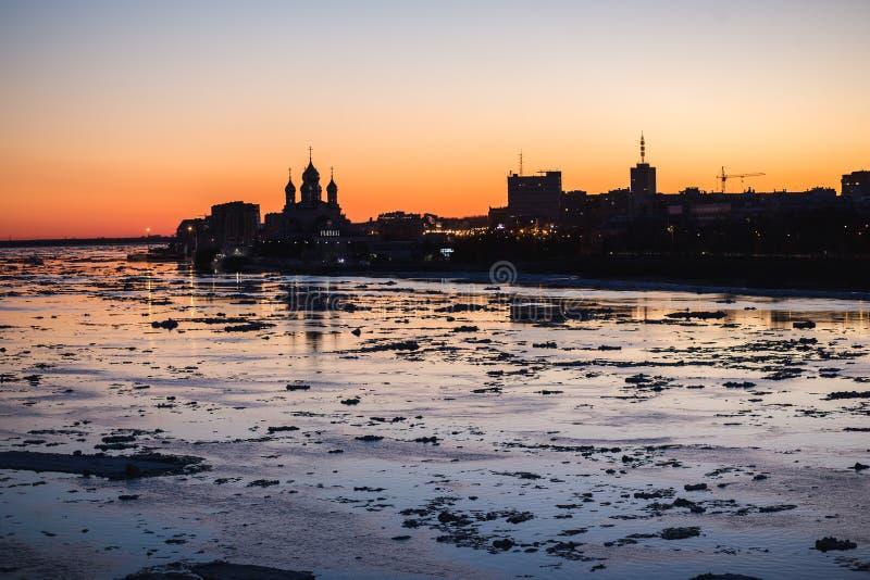 Deriva del hielo en el río septentrional de Dvina en Arkhangelsk, Rusia Citiscape hermoso de la silueta de la tarde del movimient imagen de archivo