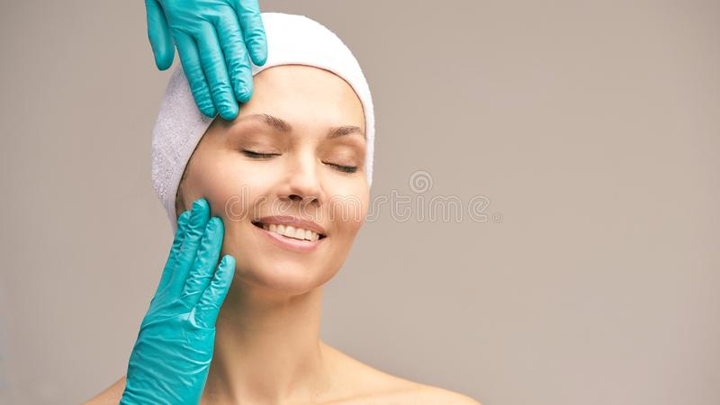 Derma rejuvenate treatment. Cosmetology face surgery. Anti wrinkle exam. Woman and doctor glove hands stock image