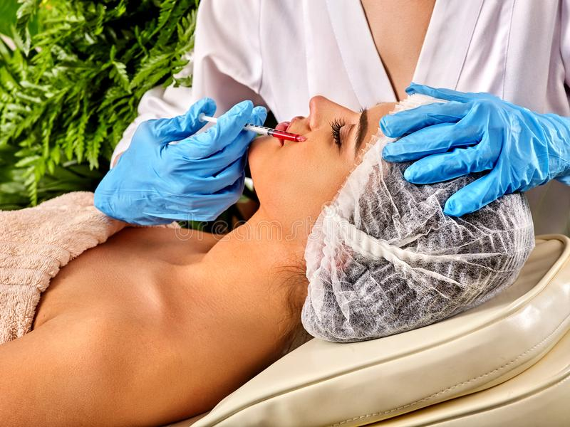 Dermal fillers lips of woman in spa salon with beautician. Filler injection for female forehead face. Plastic aesthetic facial surgery in beauty clinic stock image