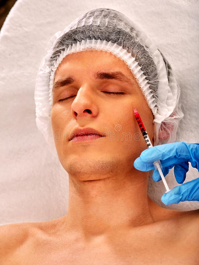 Dermal fillers of man in spa salon with beautician. Filler injection for male face. Plastic aesthetic facial surgery in beauty clinic. Man giving anti-aging royalty free stock photos