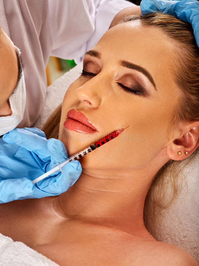 Dermal fillers of woman in spa salon with beautician. Filler injection for female forehead face. Plastic aesthetic facial surgery in beauty clinic. Beauty woman stock image
