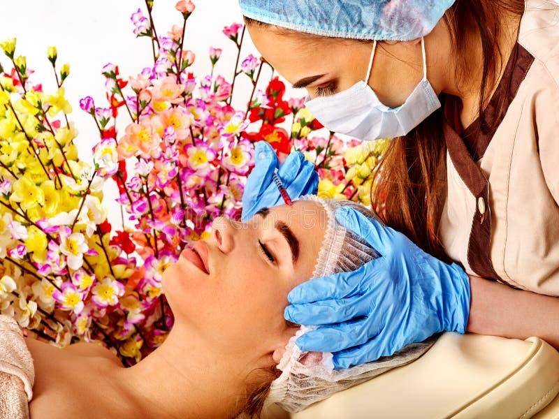 Dermal utfyllnadsgods av kvinnan i brunnsortsalong med doktorn royaltyfri fotografi