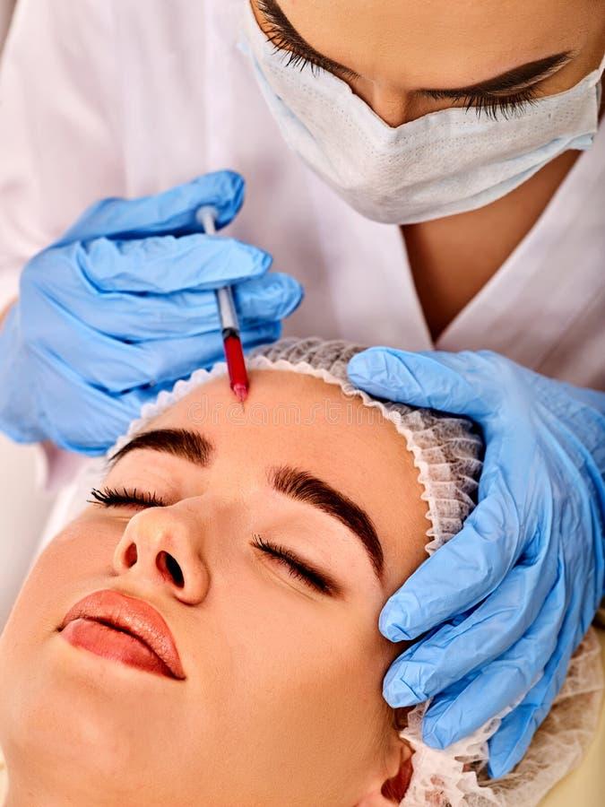 Dermal utfyllnadsgods av kvinnan i brunnsortsalong med kosmetologen royaltyfri fotografi