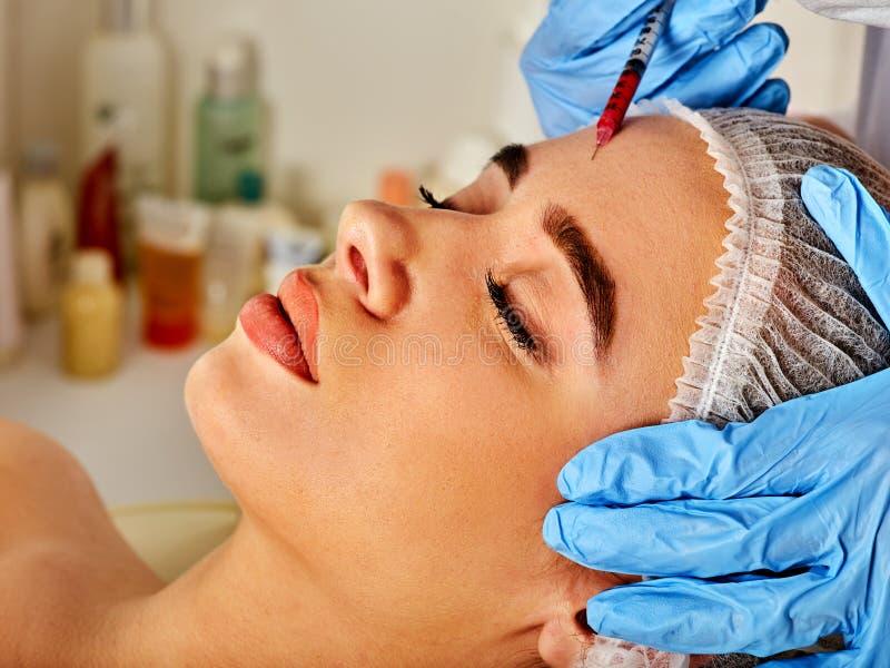 Dermal utfyllnadsgodskanter av kvinnan i brunnsortsalong med kosmetologen arkivfoto