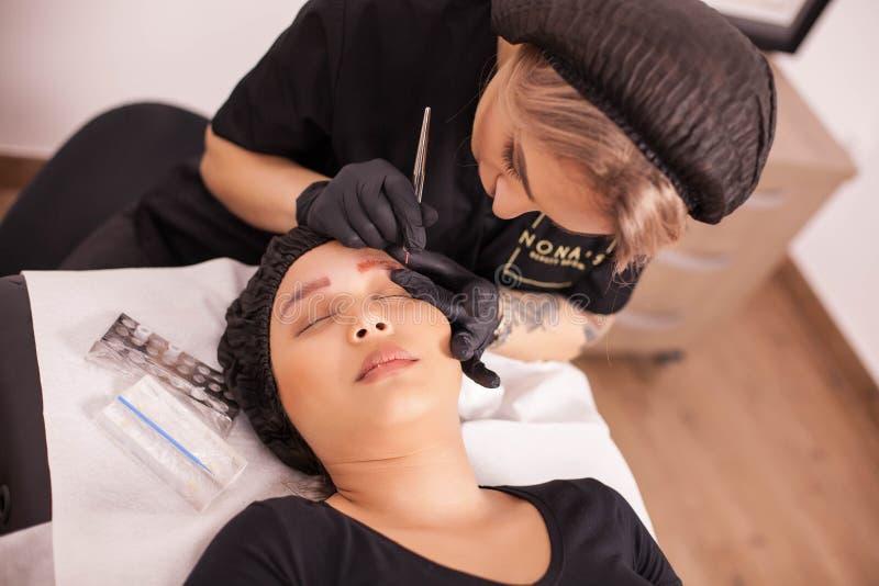 Dermatólogo de sexo femenino usando la máquina de las agujas para el retiro del tatuaje de la ceja fotografía de archivo libre de regalías