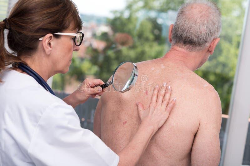 Dermatólogo que examina la piel de un paciente imagen de archivo