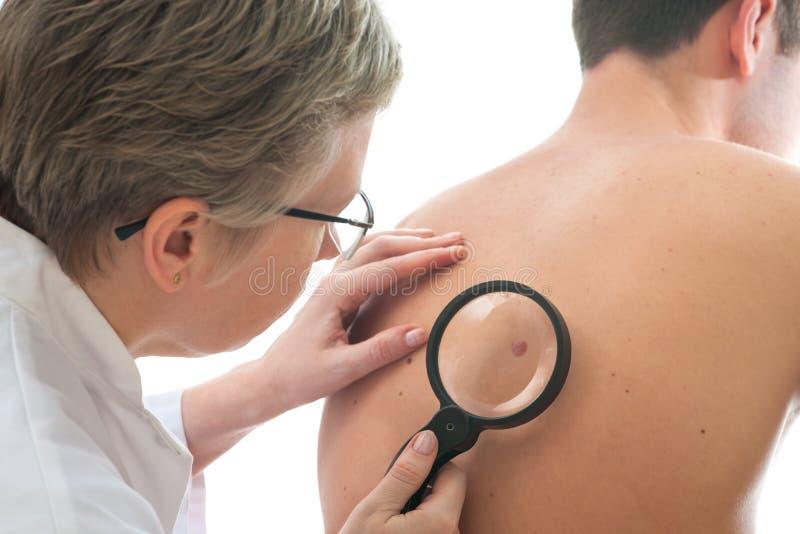 Dermatolog egzamininuje gramocząsteczki zdjęcia royalty free