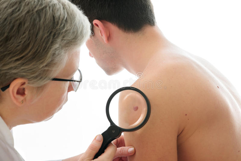 Dermatolog egzamininuje gramocząsteczki fotografia royalty free