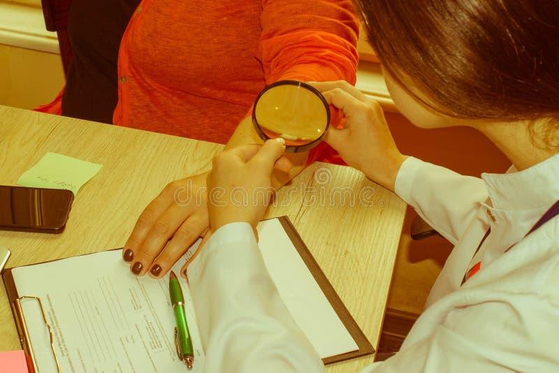 Dermatolog egzamininuje gramocząsteczki z powiększać - szkło Medyczny i opieka zdrowotna pojęcie obrazy stock