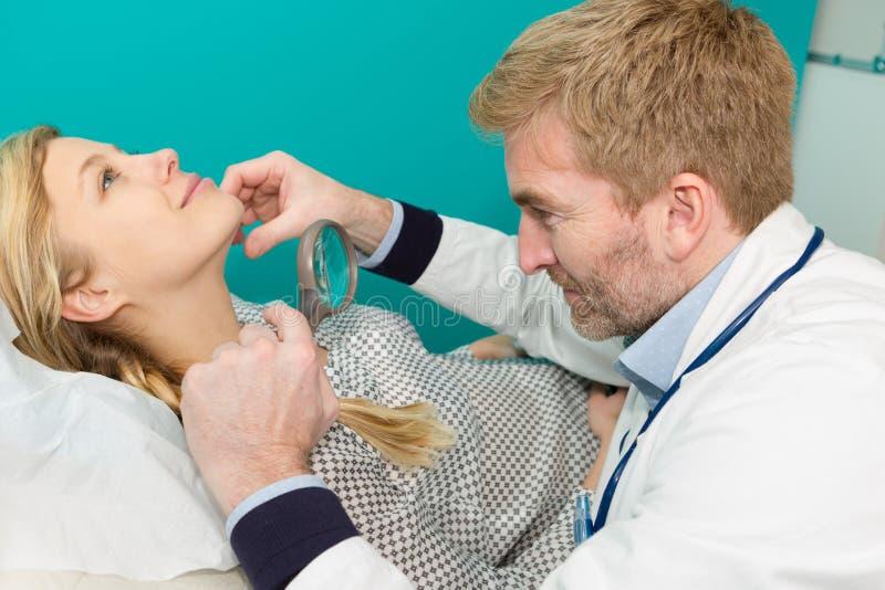Dermatolog egzamininuje gramocz?steczki z powi?ksza? - szk?o w klinice obrazy royalty free