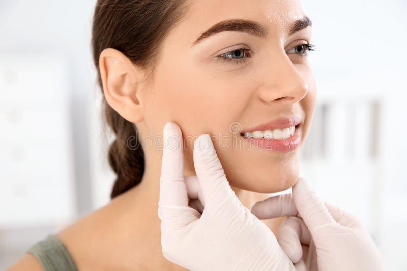 Dermatolog egzamininuje pacjent twarz w klinice zdjęcie royalty free