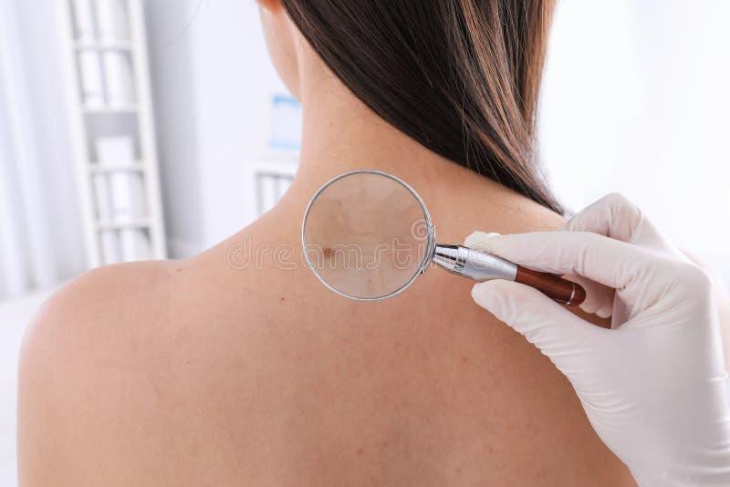 Dermatolog egzamininuje pacjenta z powiększać - szkło w klinice zdjęcie stock