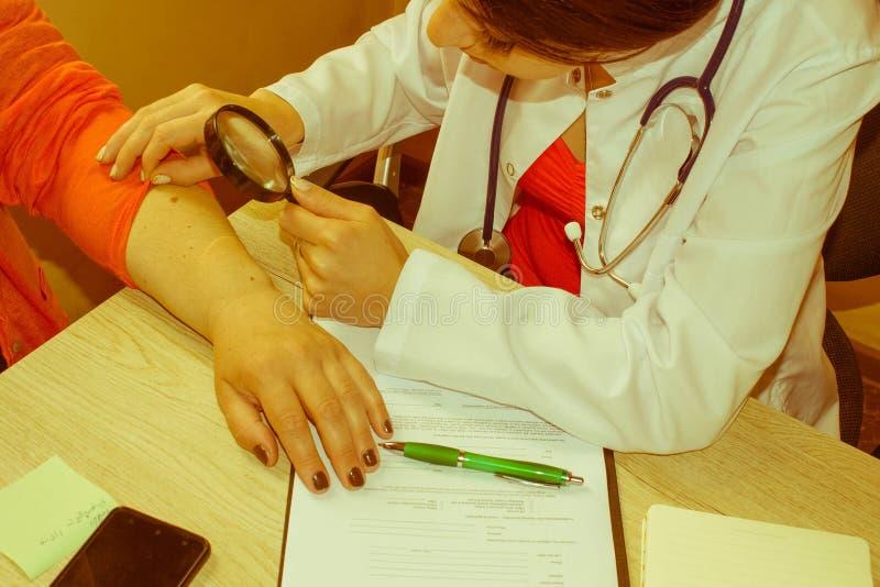 Dermatolog patrzeje kobiety ` s rękę przez powiększać - szkło Medyczny i opieka zdrowotna pojęcie obraz royalty free