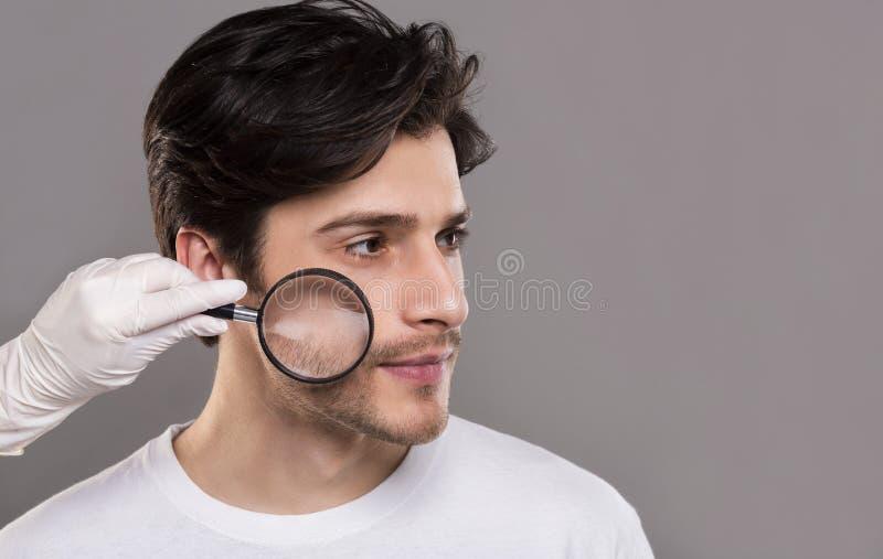 Dermatolog patrzeje młody człowiek twarzową skórę przez magnifier obrazy royalty free