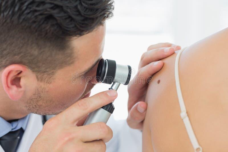 Dermatolog sprawdza gramocząsteczki na kobiecie obraz royalty free