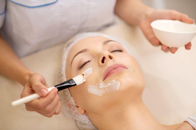 Dermatolog u?ywa kosmetyki szczotkuje podczas gdy stawiaj?cy twarzy mask? dalej zdjęcia royalty free