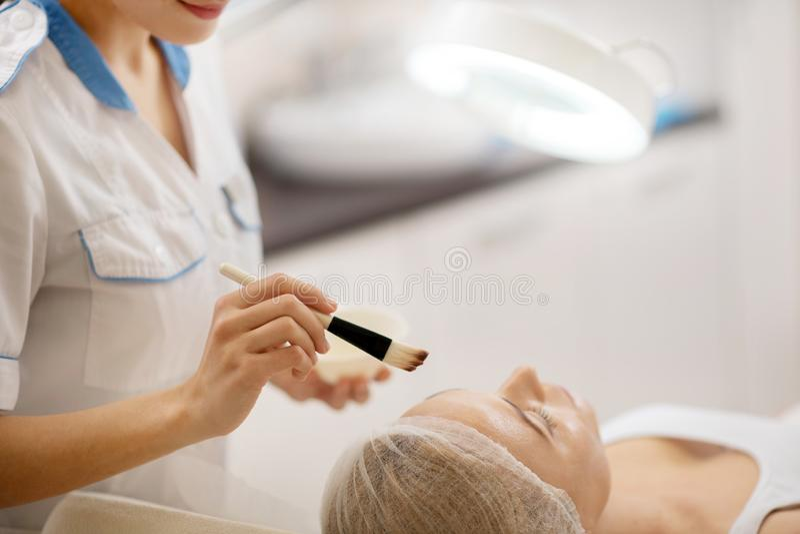 Dermatolog w bielu munduru mienia mu?ni?ciu z twarzy mask? fotografia royalty free