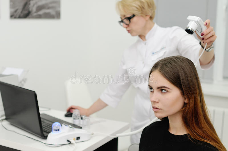 Dermatologe überprüft ein geduldiges Frauenhaar unter Verwendung eines speziellen Gerätes stockfotografie