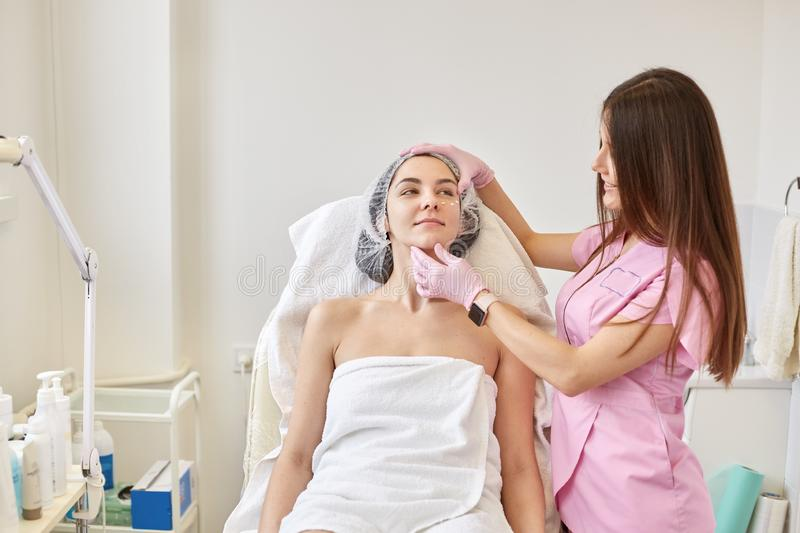 Dermatologist applying lotion around female eyes. Eye cream treatment or therapy for tired face skin. Woman wrapped with towel royalty free stock image
