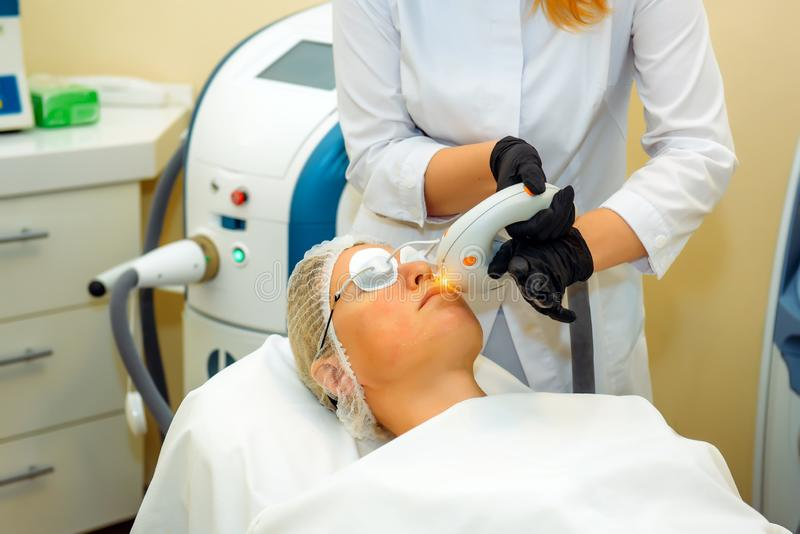 Dermatologist-cosmetologist with laser device makes facial rejuvenation procedure for a woman lying in the office of cosmetology royalty free stock photos