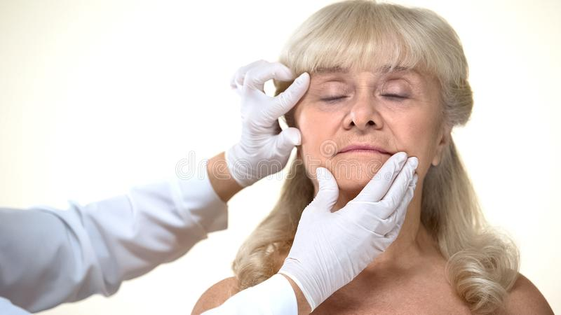 Dermatologist examining elderly female patient skin, wrinkles removal, beauty royalty free stock photography