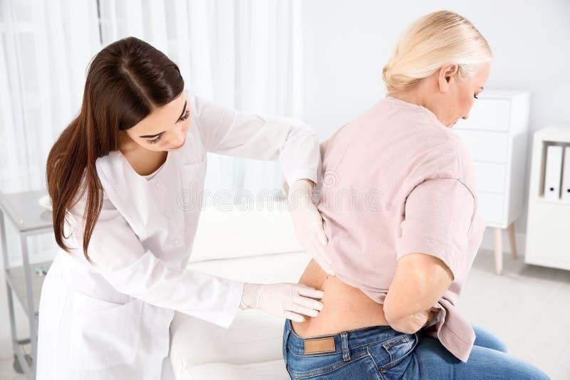 Dermatologist examining mature patient`s birthmark. In clinic stock photos